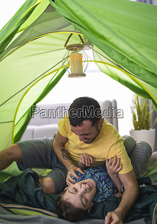 father and son in tent at