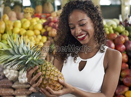portrait of smiling woman with pineapple