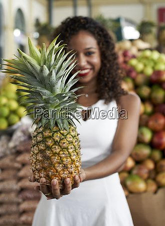 womans hand holding pieneapple at market