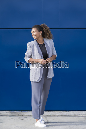 smiling businesswoman in front of blue