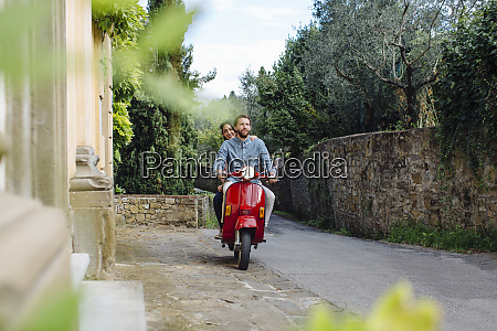 man with girlfriend riding on vespa