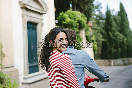 smiling woman sitting with boyfriend on