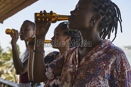young woman drinking beer while standing