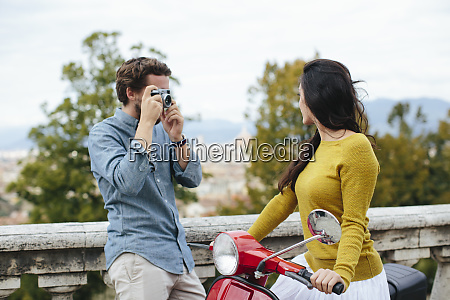 young man photographing girlfriend sitting on
