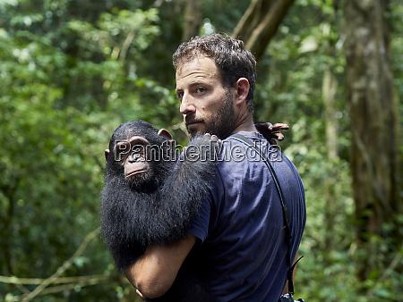 cameroon pongo songo man carrying chimpanzee
