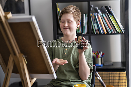 boy showing via smartphone painting to