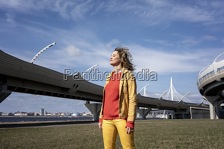 smiling woman with windswept hair standing