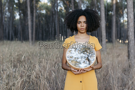 young woman with afro hair holding