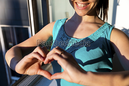 laughing woman making heart shape with