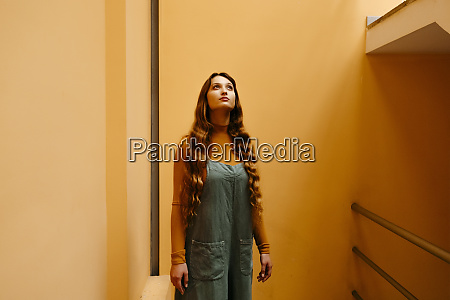 young woman wearing jumpsuit leaning on