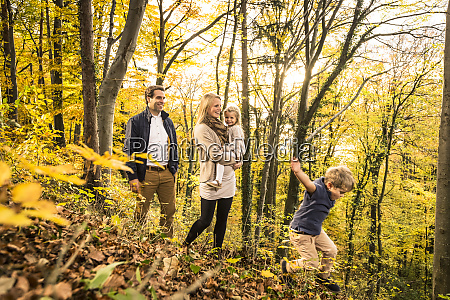 family enjoying in forest during autumn