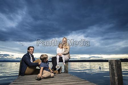 full length of happy family sitting