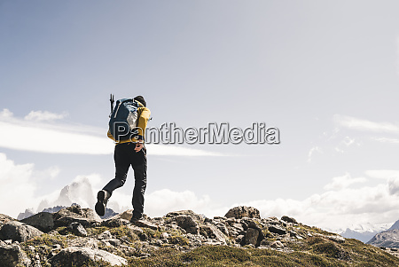 man with backpack walking on mountain