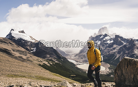man walking on mountain against cloudy