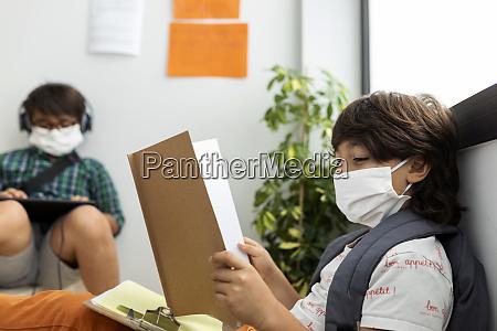 boys wearing masks studying while sitting