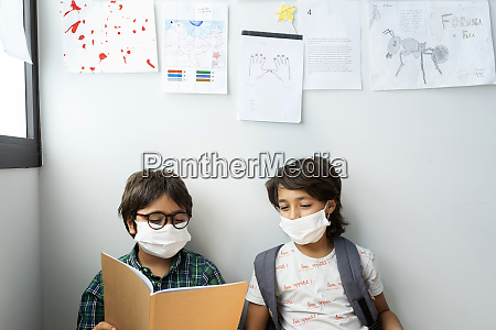 boys wearing masks reading book while