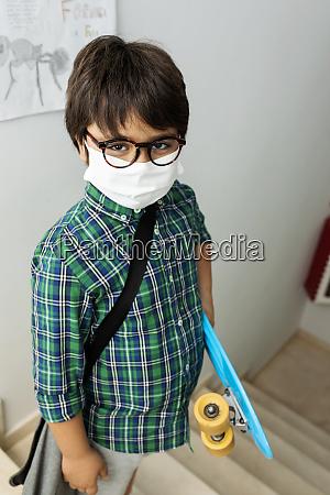 boy wearing mask holding skateboard while