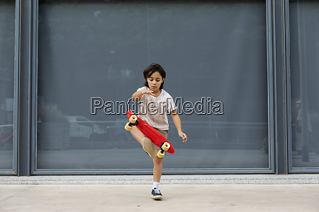 boy practicing stunt with skateboard while