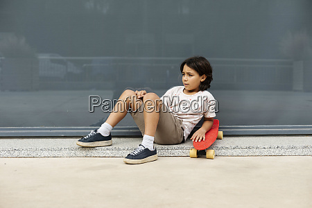 thoughtful boy with skateboard relaxing on