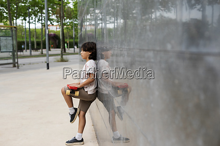 boy holding skateboard looking away while
