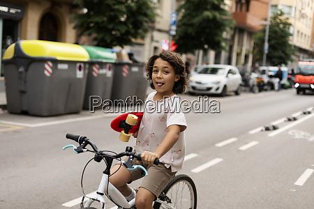 carefree boy holding skateboard while riding