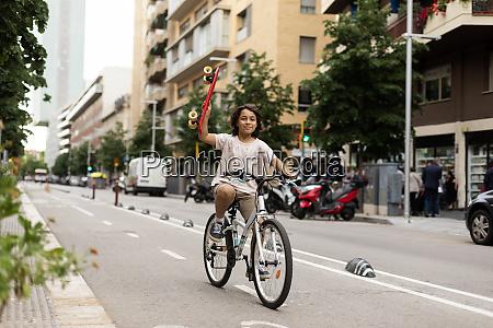 smiling boy holding skateboard while riding