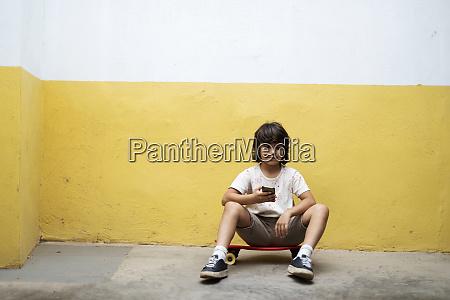 boy using smart phone while sitting