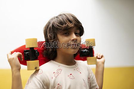 close up of boy holding skateboard