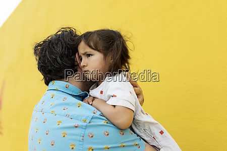 father consoling unhappy little daughter