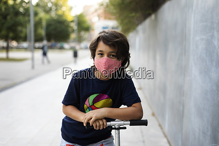 portrait of boy with scooter in