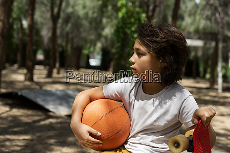 thoughtful boy with basketball and skateboard