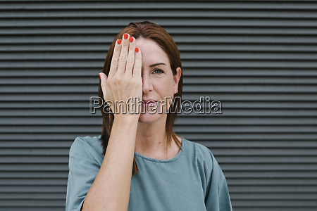 woman covering one eye with her