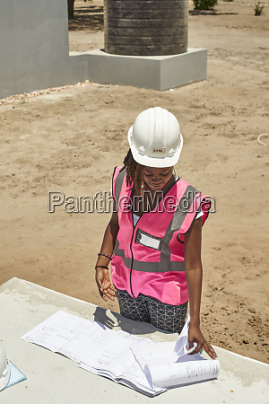 female building contractor analyzing blueprint on