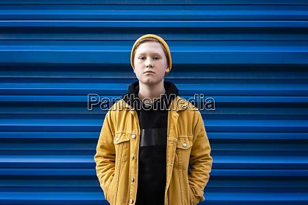 confident boy standing against blue shutter