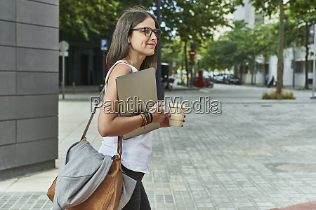 thoughtful businesswoman holding laptop and disposable