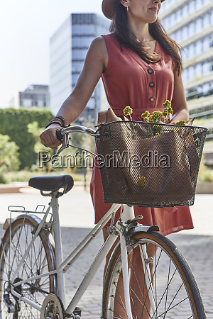 woman standing with bicycle on city