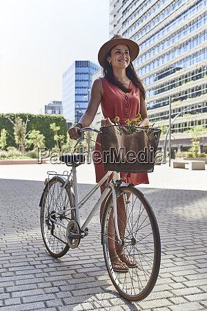 happy woman standing with bicycle on
