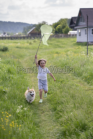 playful boy holding butterfly net while
