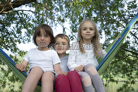 cute children sitting on hammock in