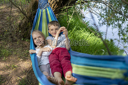 cute children relaxing on hammock in
