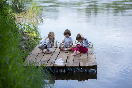 happy children playing on pier over