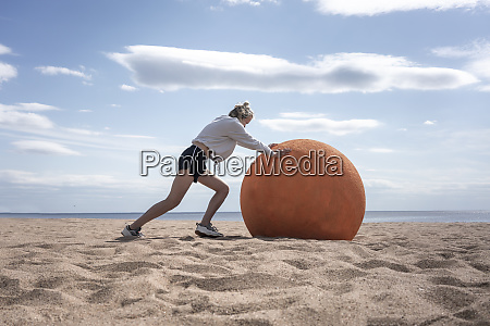 young woman rolling orange stone at