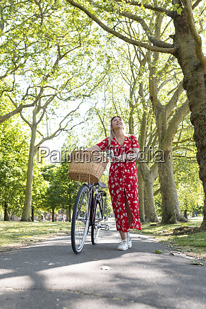thoughtful woman walking with bicycle on