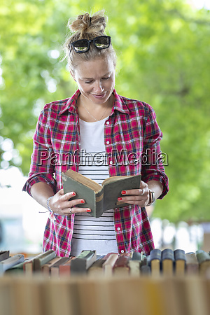 mid adult woman reading book while