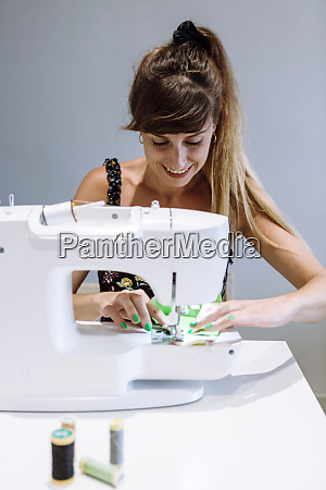 smiling female tailor sewing mask in