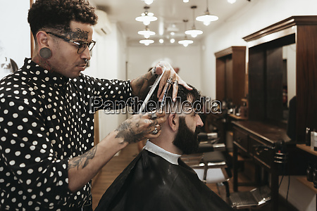 fashionable hairdresser styling mans hair at