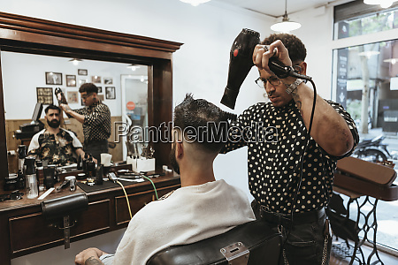 trendy hairdresser blow drying mans hair