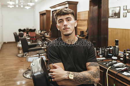 trendy hairdresser standing arms crossed at