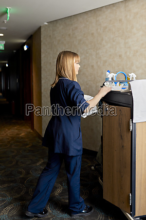 chambermaid arranging cleaning products on push