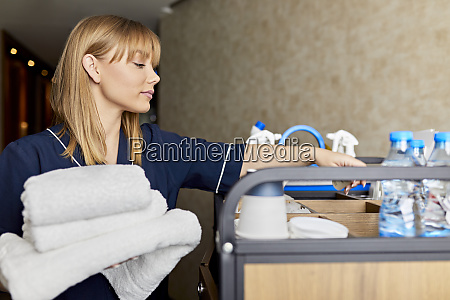 chambermaid holding towels while standing with